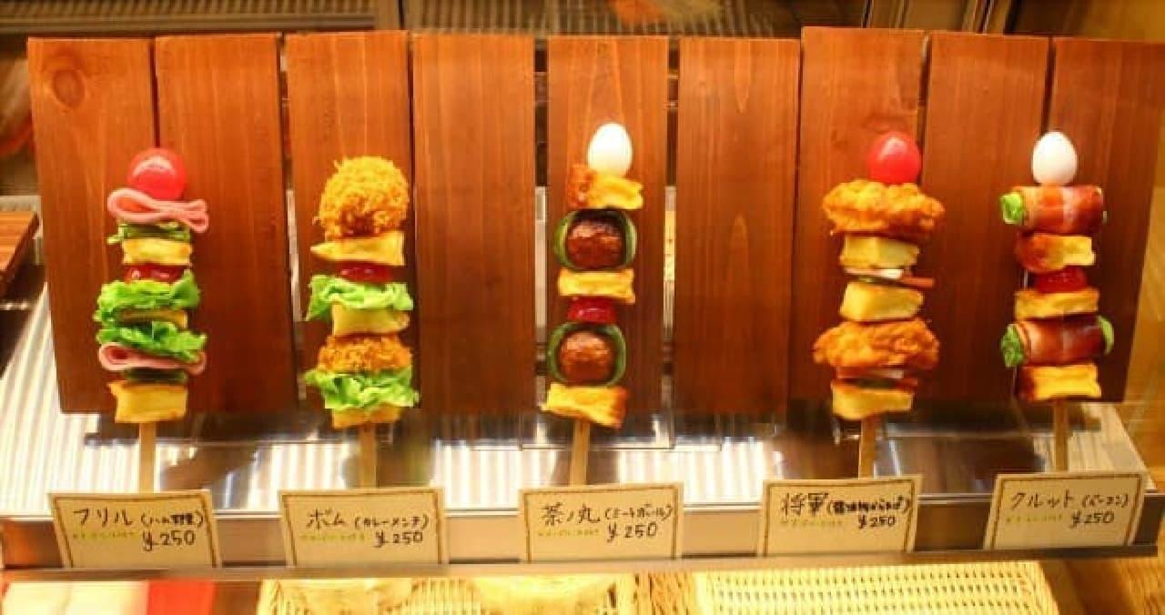 ショーケースに並ぶ串サンドの見本