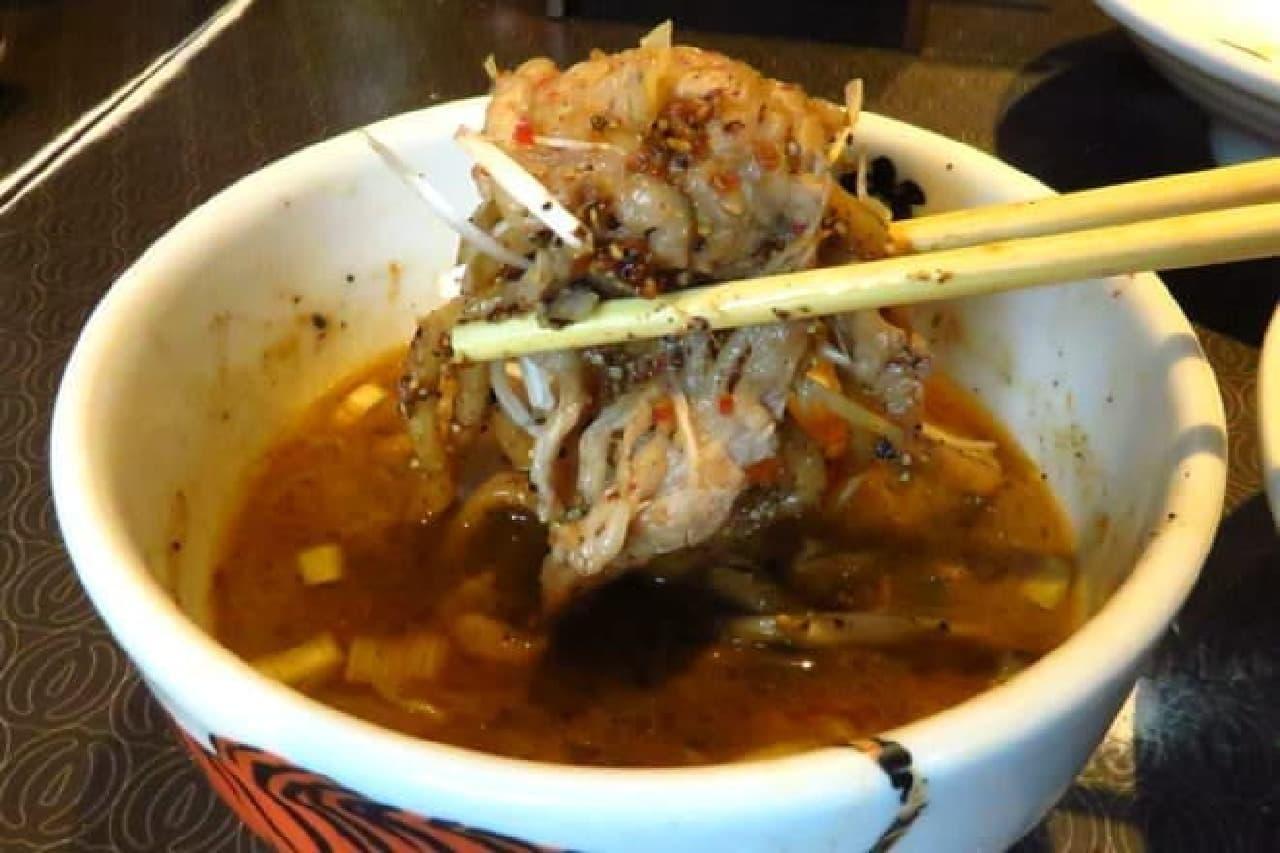 牛肉、ネギ、麺を、ともにスープにつけて