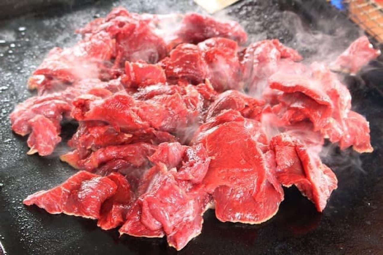 真っ赤なダチョウ肉。コンロのまわりに人が集まる