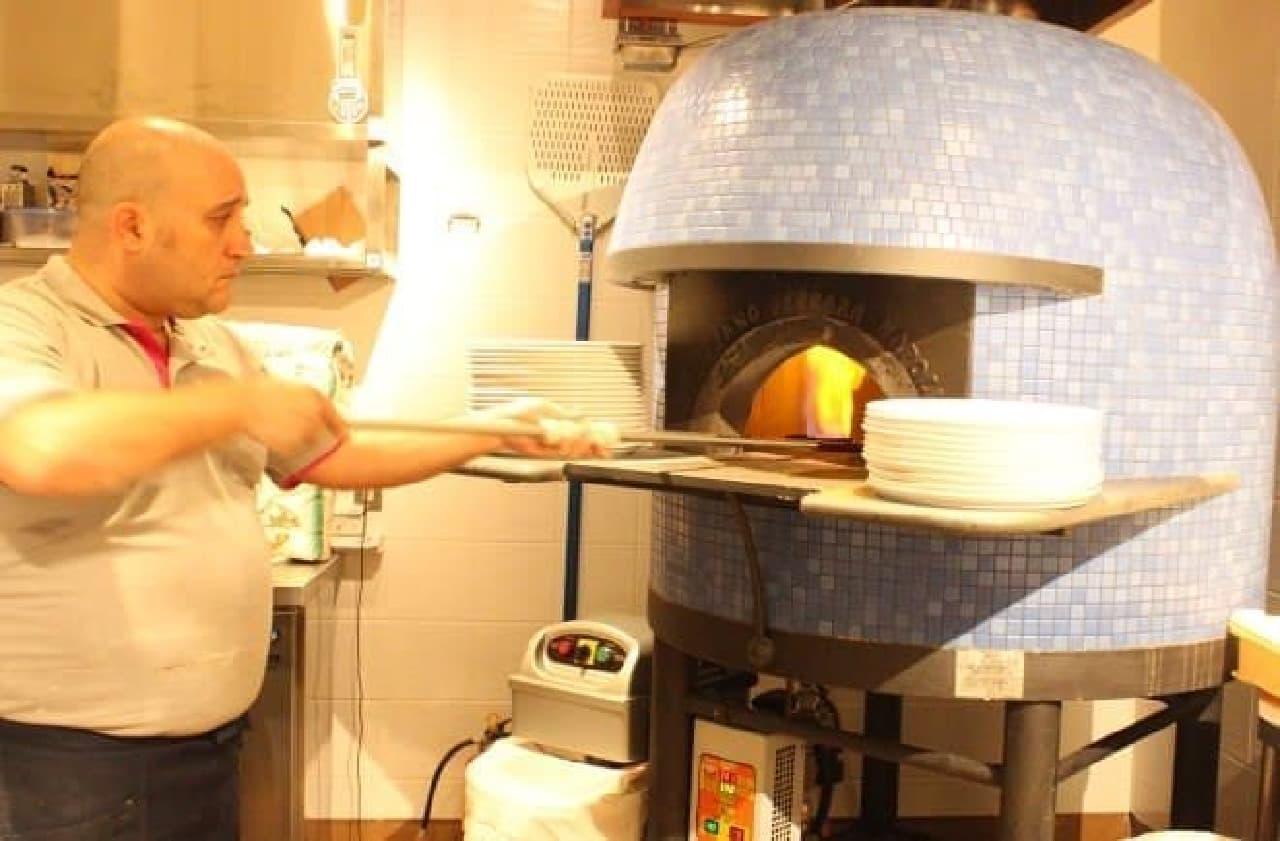 ピッツァイオーロのマリオさんが、特注の石窯で焼き上げる