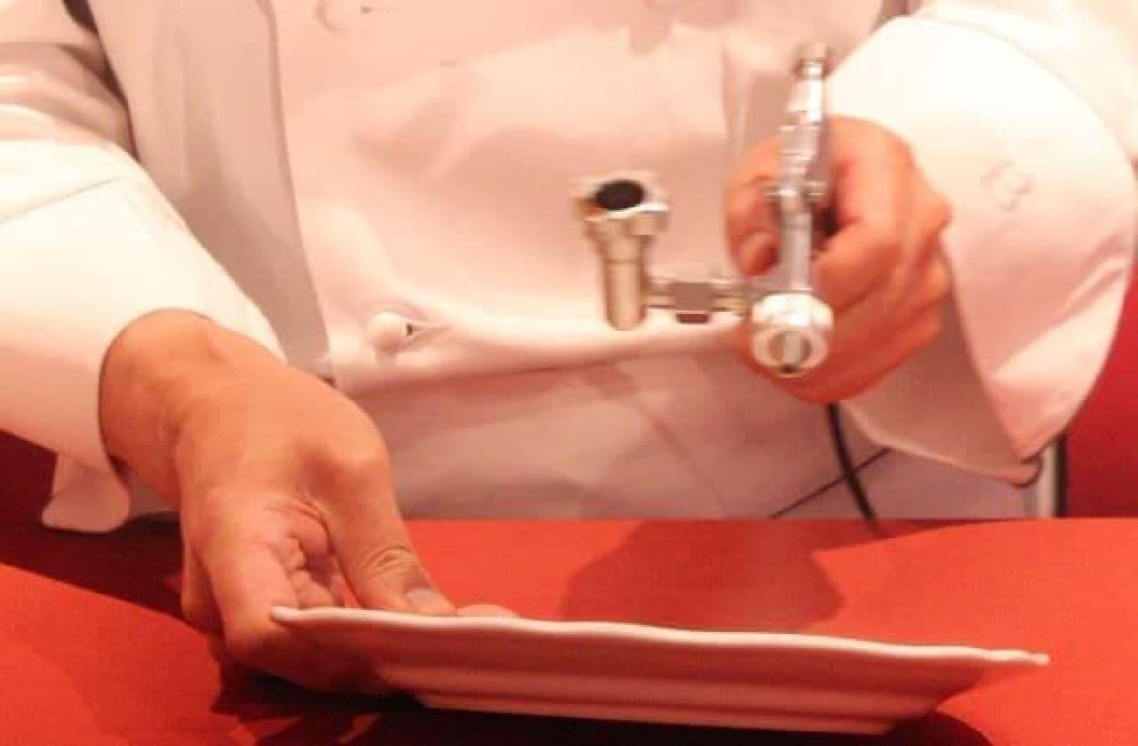 専用の機械を使ってチョコレートバーにチョコを吹きつけメッセージをデザインする