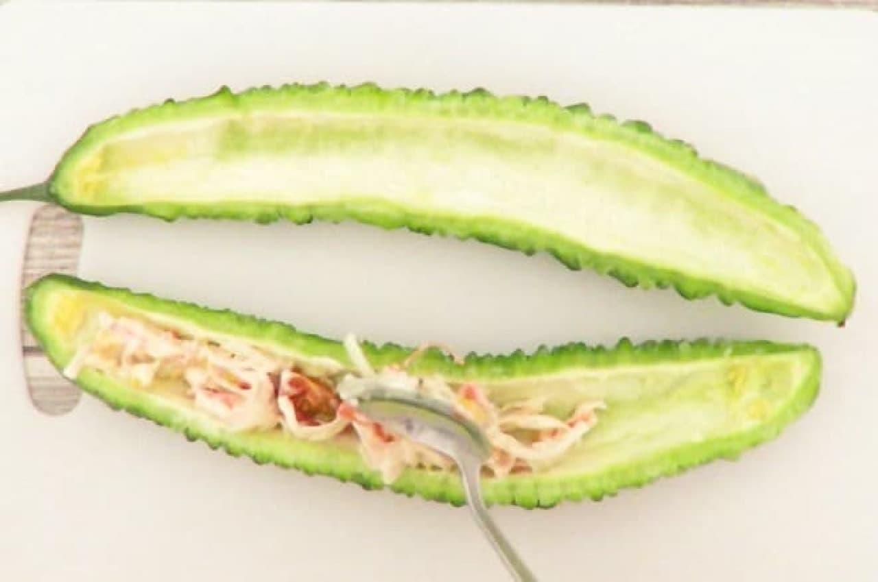 ゴーヤにミニトマト、サラダかまぼこ、コーンマヨネーズを詰めるところ
