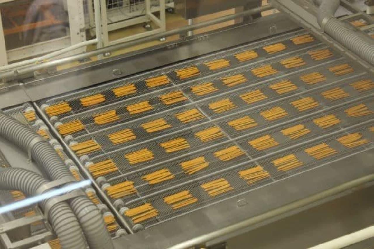 焼かれてマシンの上を流れていくプリッツ