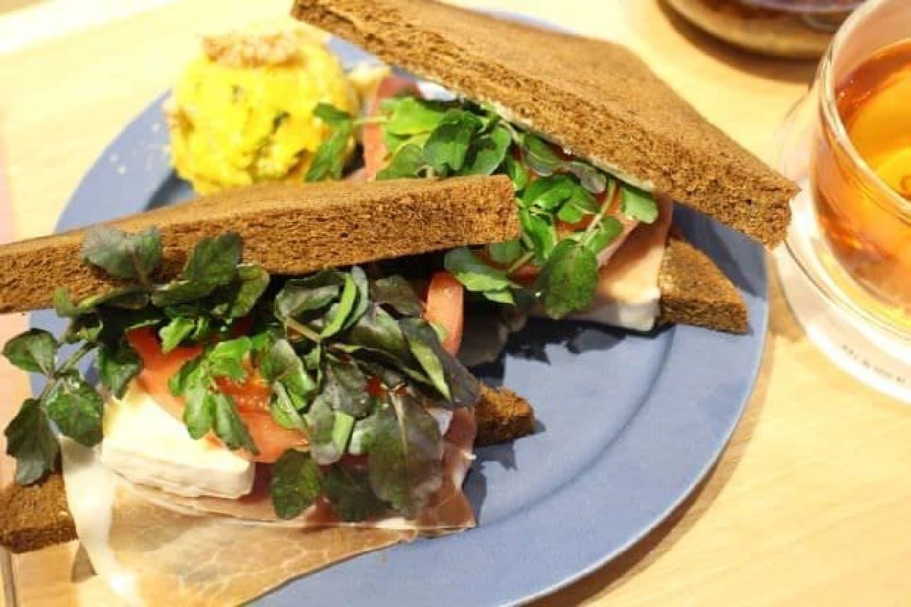 なめらかチーズと生ハムのサンドウィッは 黒パンにクレソン、カマンベール、チーズ、生ハムなどをサンドしたサンドゥイッチ
