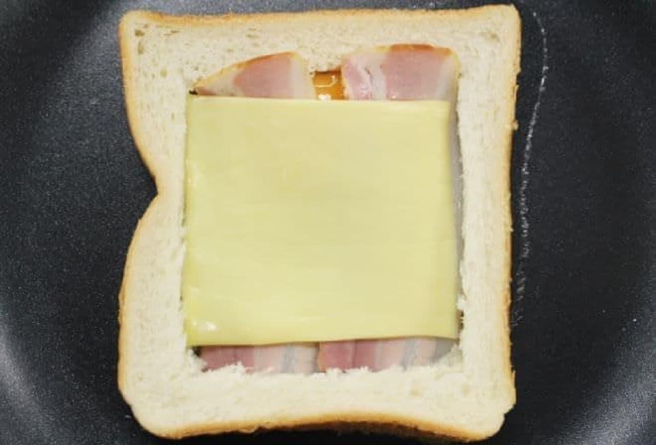 食パンの中に卵、ベーコン、チーズを落とした様子