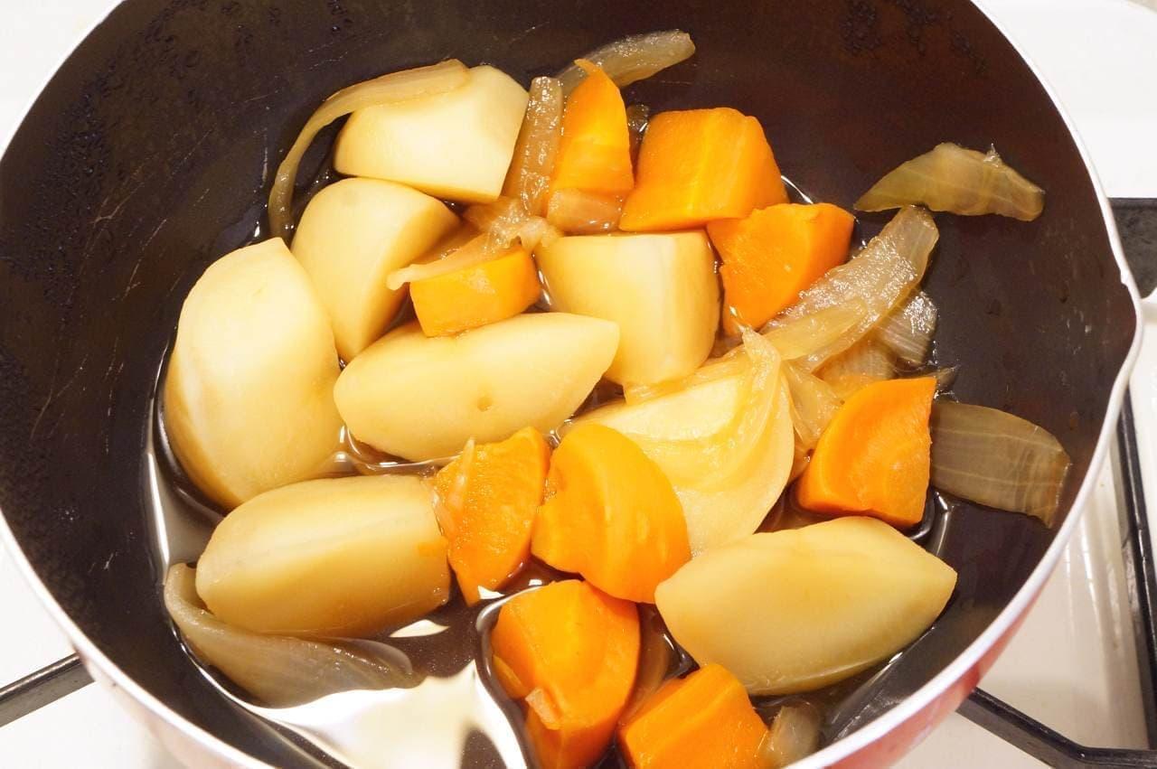 鍋に入ったじゃがいも、にんじん、玉ねぎ