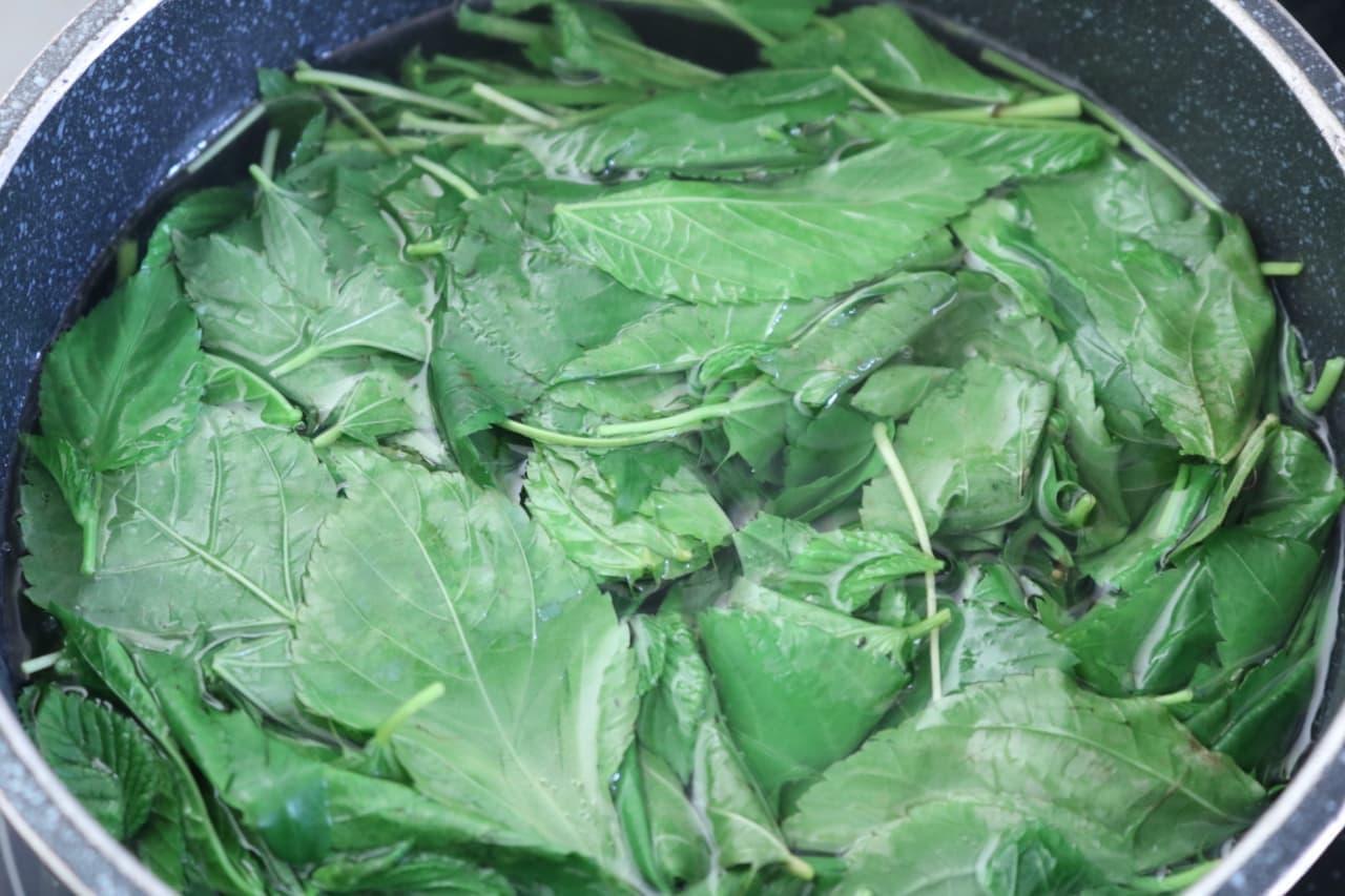 ステップ6続けて葉を入れ、箸で軽く沈ませてさらに20秒ほど茹でます。