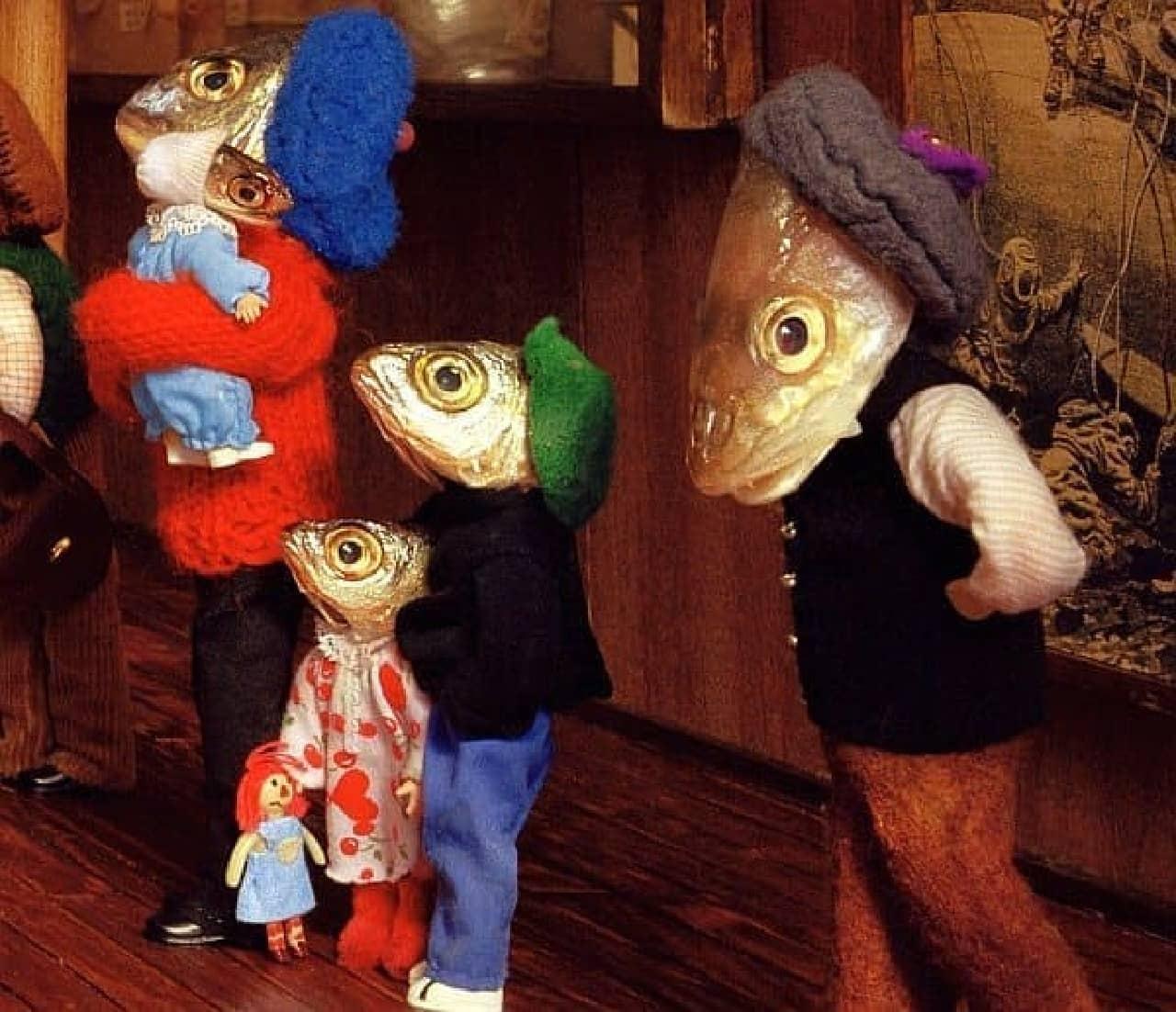 こちらは家族  赤ん坊は魚だが、子どもが手にしている人形は人間