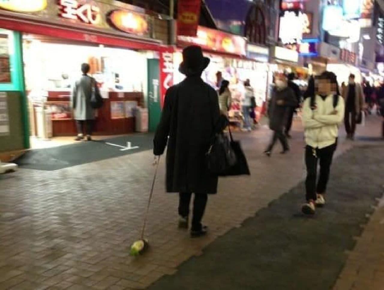 大根を散歩させる黒ずくめの男   [写真提供:@WwwwwPiyo さん]