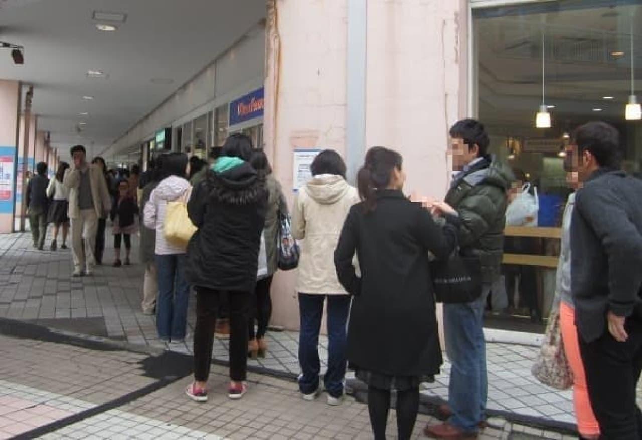 行列は、ショッピングセンターの外壁を沿うように伸びていました