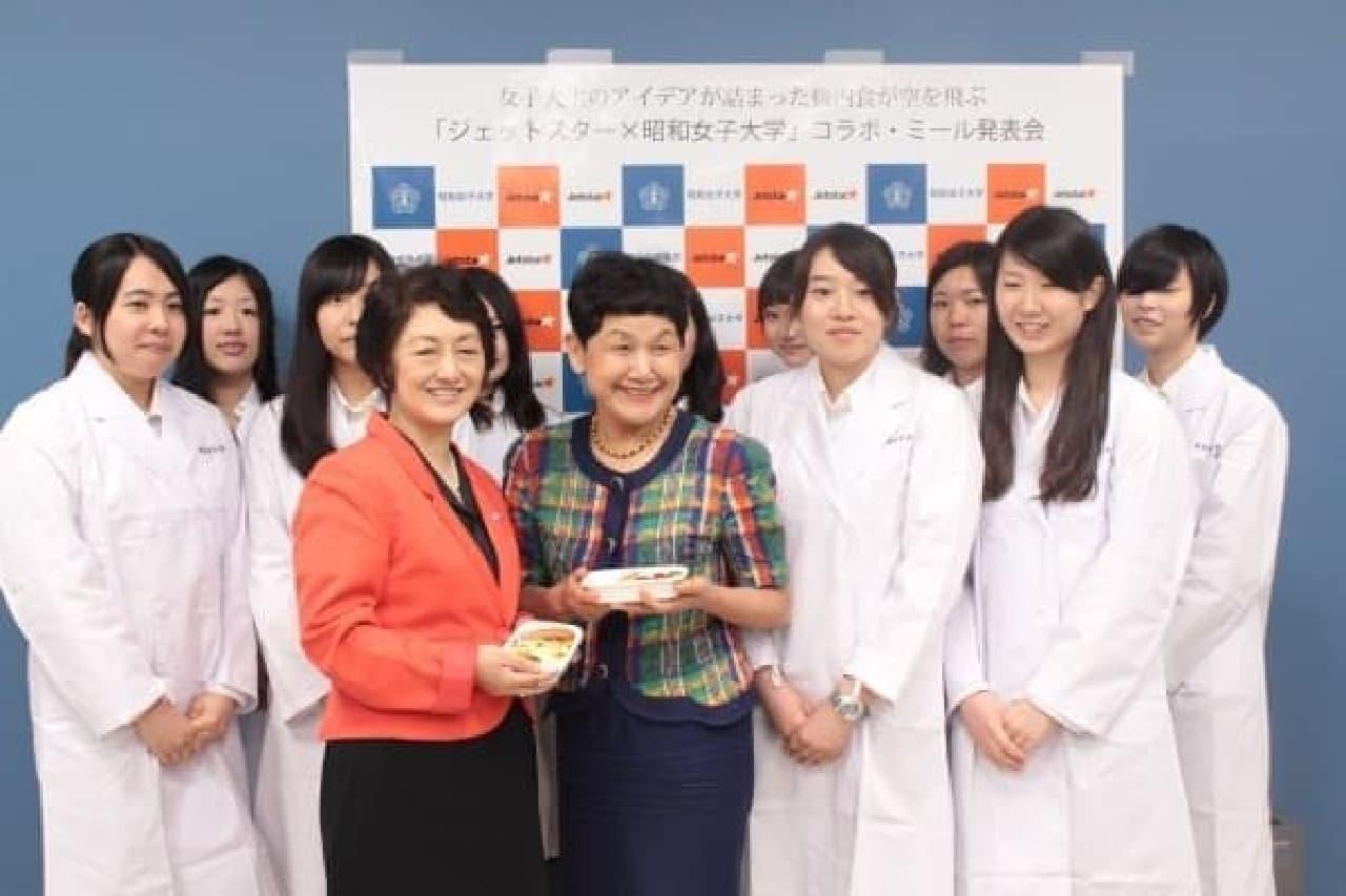 ジェットスター・ジャパン鈴木社長(中央左)と昭和女子大の坂東学長(中央右)を  プロジェクトに携わった学生たちが取り囲む