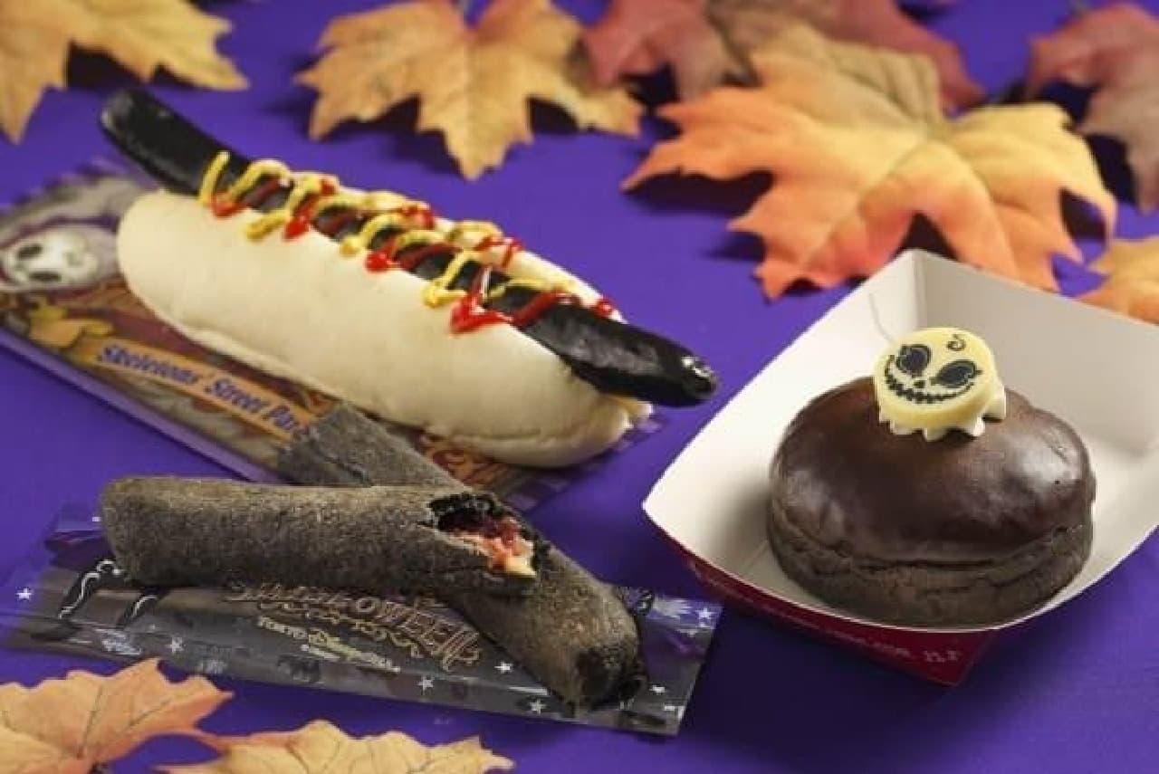 東京ディズニーシーの各レストランで提供される限定メニュー  ブラックソーセージドッグ(左奥)、ブラックティポトルタ(左手前)、オレンジクリームドーナツ(右)