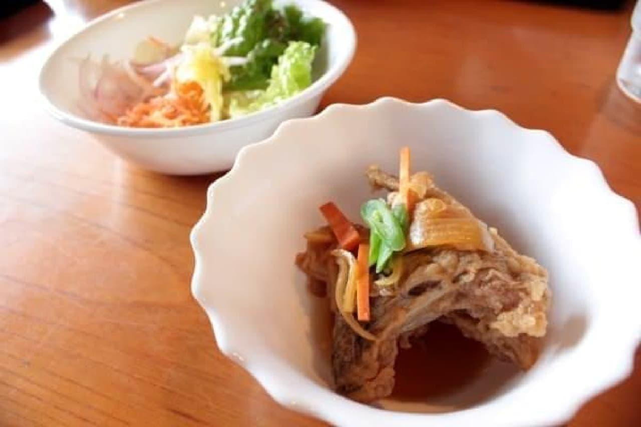 鯛のカマの南蛮漬け(手前)と、  島で作られた野菜のサラダ(奥)