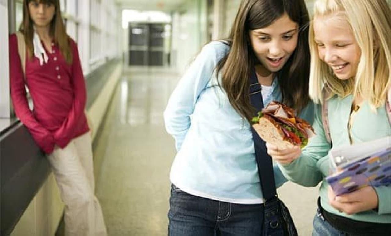 学校の廊下で写真を見る学生